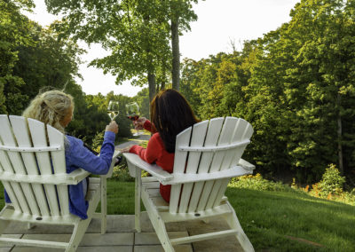 Two women toasting on patio chairs 2U7A7722 web